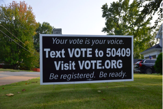 A yard sign encourages eligible voters to register and use their voice.
