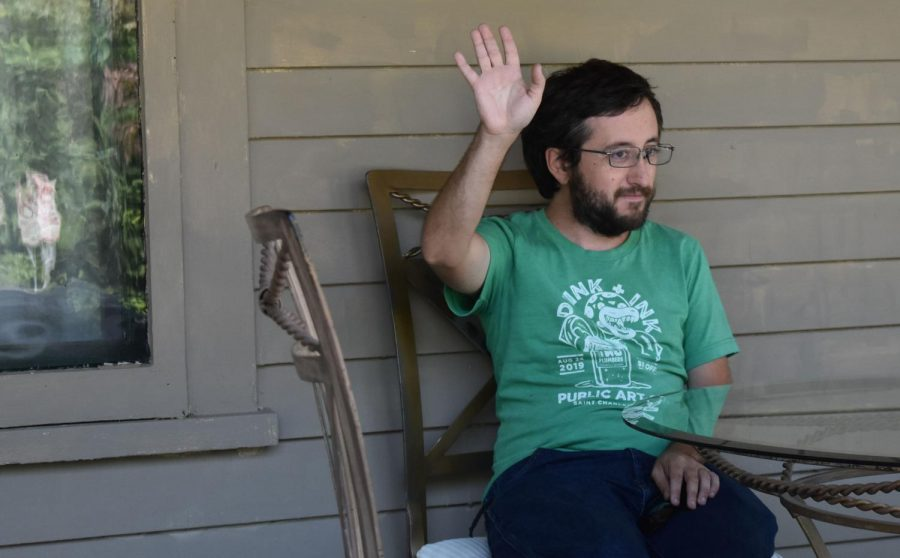 Steve Fredericks, 32, waves to his neighbors on the front porch of his house.