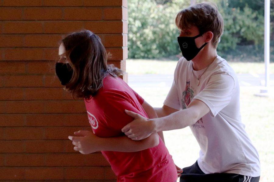 Xander Piskulic, senior, holds back Cooper Menne, sophomore, in a scene at a cast rehearsal outside KHS.