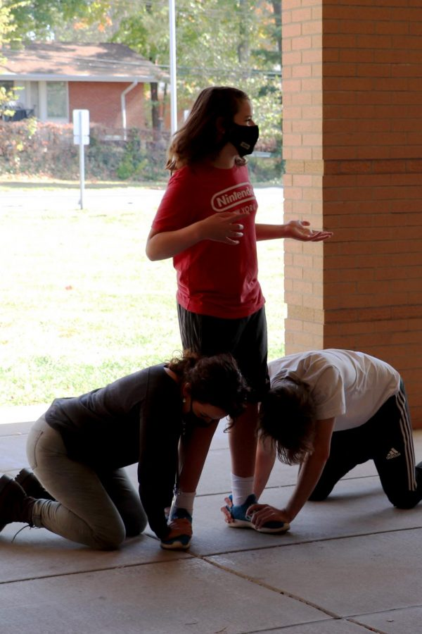 Kelly Schnider, director, and Xander Piskulic, senior, hold down the feet of Cooper Menne, sophomore, in order to help him stand still during a scene.