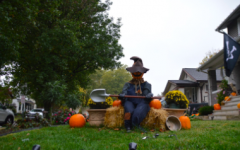 A pumpkin man sits on a barrel of hay with a shovel.