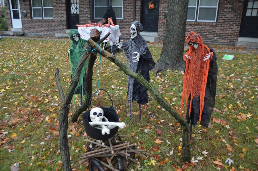 Three skeletons surround a cauldron and are placed amongst other props and decorations.