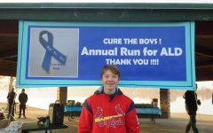 Nicholas Purschke stands in front of the Annual Run for ALD sign. Photo courtesy of the Purschke family.