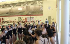 The seniors lead the rest of the team in a cheer before the meet starts.