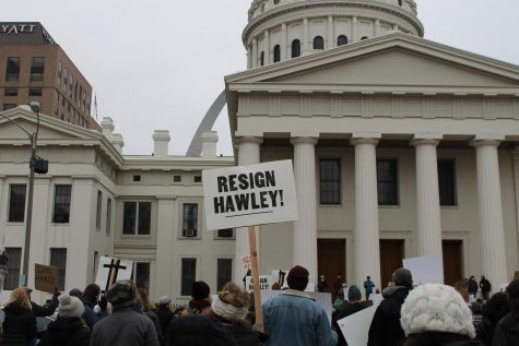 "A protester holds a ""Resign Hawley!"" sign as people gather to listen to several speakers from the crowd."