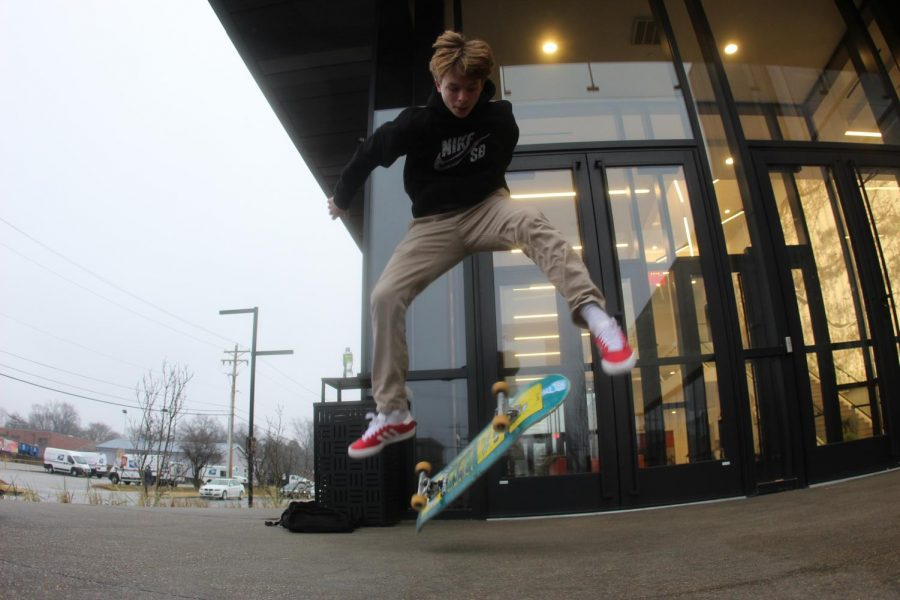 Ryder George-Lander in mid-air doing a kickflip trick on his skateboard.