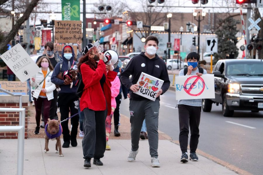 Organizers Peyton Nico and Wyatt Byers lead the front of the march as the group passes Kirkwood city hall.