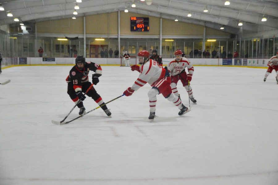 Charlie Munroe reaches for a puck in the boys varsity game against Chaminade.