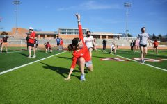 Athletes participate in warmup drills on the turf during in-person preseason workouts.