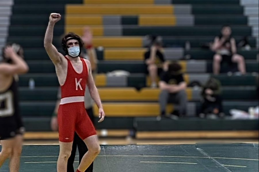 Ethan Gjelvik celebrates his victory after pinning down his opponent.