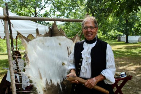 Lawrence Micheal stands in front of the deer hide he is using as an example at the folk festival.