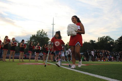Jaida Autry, senior, walks a Unified Night Lights member up the field to start off the night.