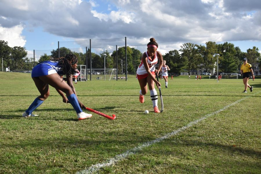 Ellie Francois, junior, runs with the ball as a Westminster player dives for it.