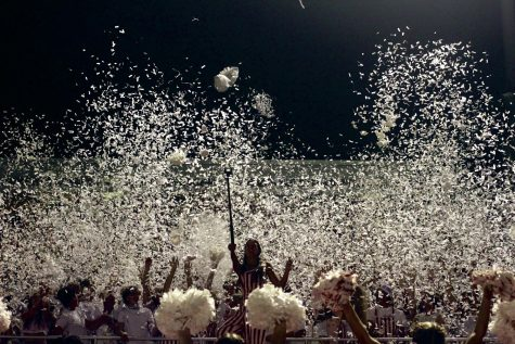 The students section throws white confetti in the air to celebrate the whiteout theme.