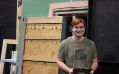 Jack Herwig stands in front of the disassembled show set with the clipboard he used during his performance.